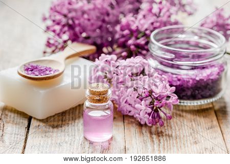 take bath with lilac cosmetic spa set and blossom on woode table background