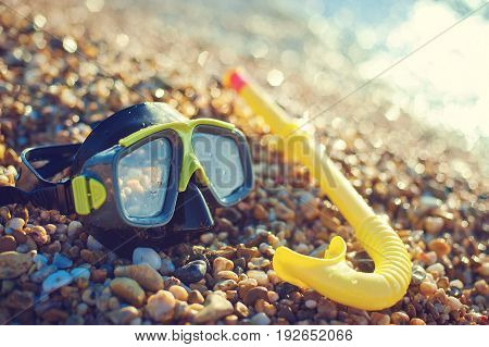 The blue mask for diving and the tube lie on the beach, on the sand. The concept of tourism and travel.