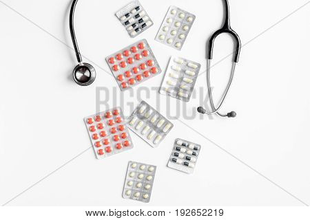 doctor's work place with stethoscope and pills on hospital desk background top view