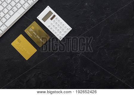 accountant work desk with credit card and calculator for online payment on dark background top view space for text