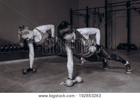 Two fit women in gym doing fitness exercises with dumbbells staying in plank pose, black and white.