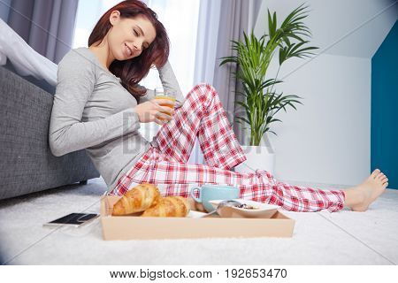 Portrait of happy  woman eating breakfast in bedroom, smiling and healthy