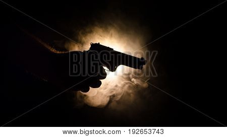 Male Hand Holding Gun On Black Background With Smoke ( Yellow Orange Red White ) Colored Back Lights