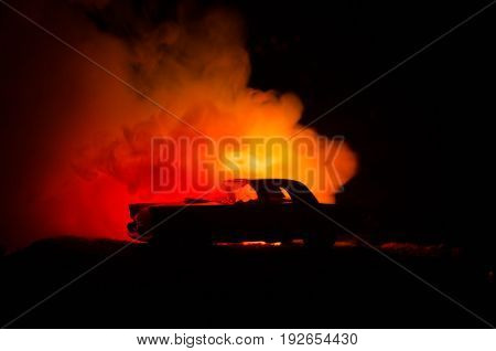 Burning Car On A Dark Background. Car Catching Fire, After Act Of Vandalism Or Road Indicent