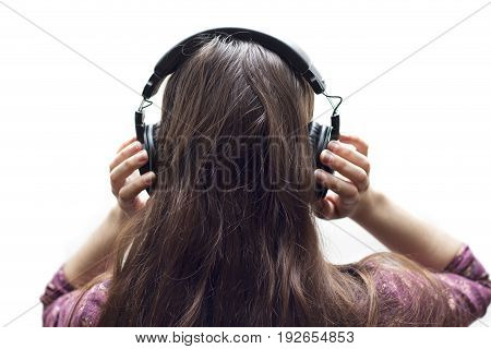 Rear view closeup of young girl listening to music with stereo headphones on white background.