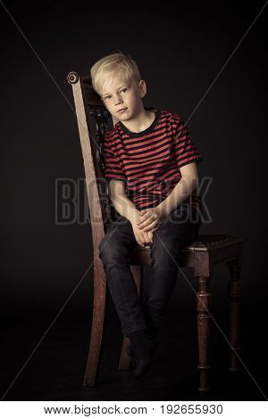 Calm Thoughtful Little Boy Sitting On A Chair