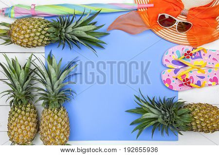 Beach accessoryhatsunglassesshoesumbrella and pineapple on white wooden concept summer holiday background and summer sale