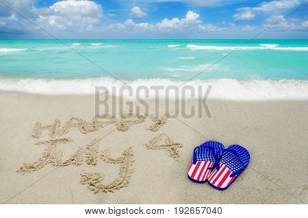Independence USA background with flip flops of American flag colors on the sandy beach near ocean