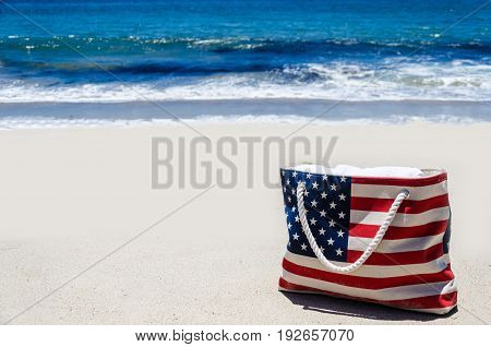 Bag with American flag colors near ocean on the sandy beach - USA patriotic holidays background