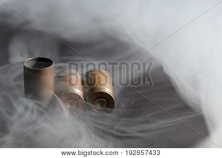 Three Empty Bullet Casings From Pistol Cartridges In Thick Smoke