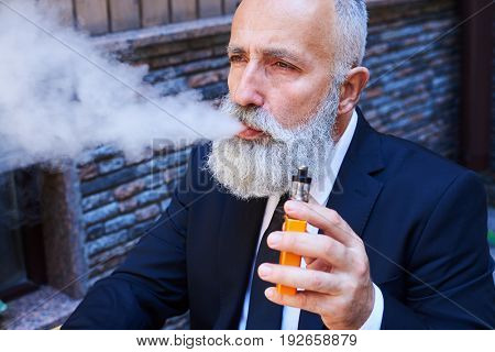 Close-up of good-looking sir exhaling fume while smoking electrocigarette