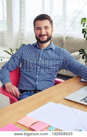 Vertical of smiling man with beard relaxing while working at home