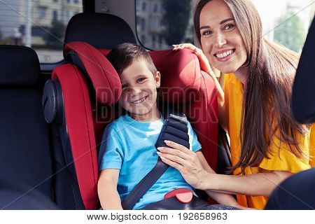 Mid shot of smiling mother checking seat belt of son sitting in baby seat