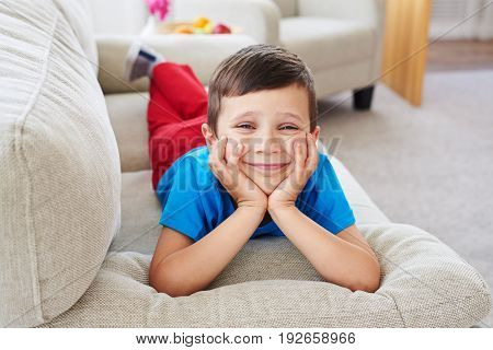 Close-up shot of small boy leaning on his hands, cute expression. Boy in bright clothes lying on sofa