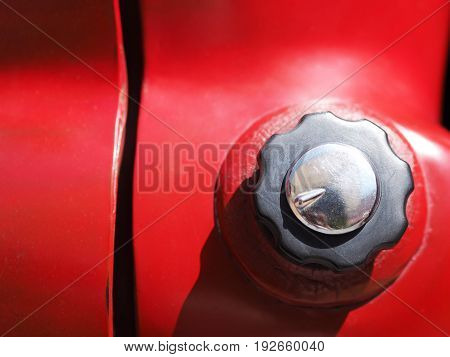 Close up fuel gas cap of red old sport car.