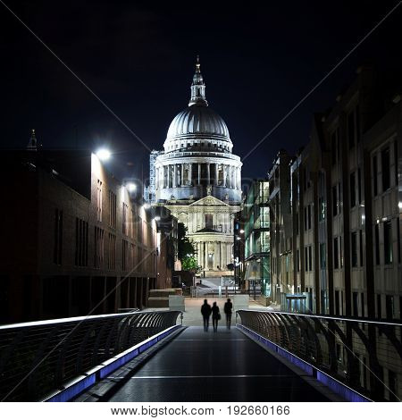 St Paul's Cathedral at night, as seen from the Millennium Bridge. Late night pedestrians can be seen silhouetted in the foreground.