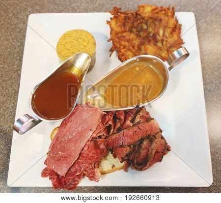 Famous Corned Beef and Pastrami on rye sandwich served with potato latke and kishka in New York Deli
