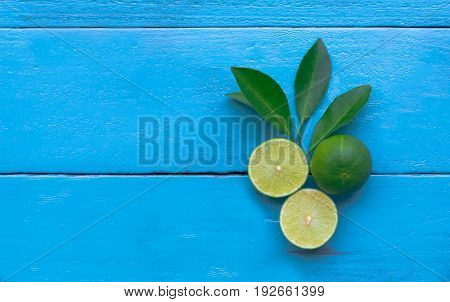 The Lime Lemon Are Half Cut On Blue Wooden Background. Copy Space For Graphic Designer