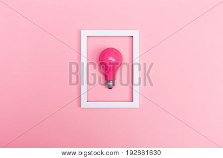 Colored lightbulb on a pink background with frame