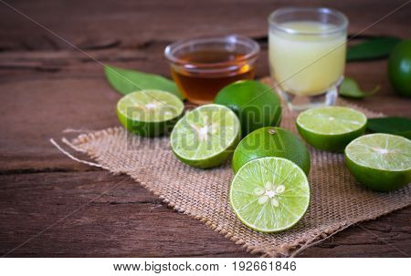 A Lime Lemon With Juice  And Honey In Transparent Glass With Sack Cloth On Rustic Wooden Background.