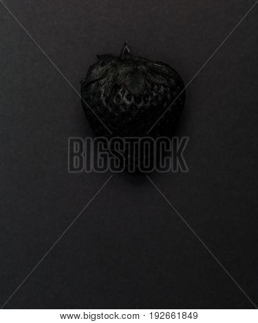 Painted black strawberry on a black background