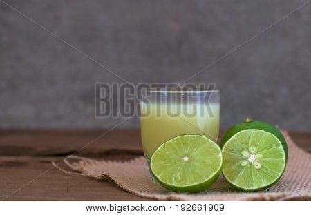 A Lime Lemon And Juice In Transparent Glass With Sack Cloth On Rustic Wooden Background. Copy Space