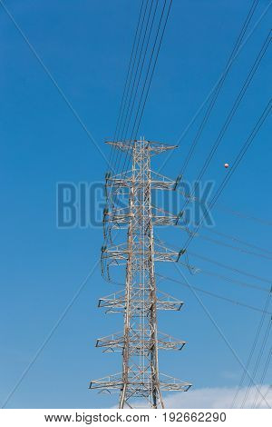 high voltage electrical tower blue sky background.