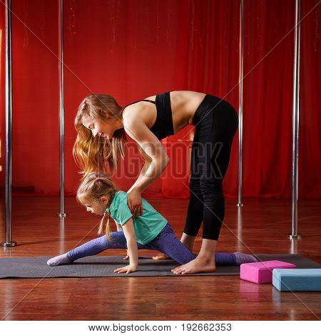 The coach helps the little girl to sit on the twine. A healthy lifestyle since childhood. Flexibility