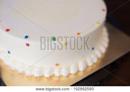 delicious vanilla cream cake on wooden table