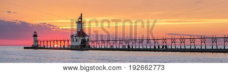 On the Summer Solstice the sun sets on Lake Michigan between the Inner and Outer North Pier Lighthouses at St. Joseph Michigan. The lights catwalk and people are silhouetted by an dramatic sunset.