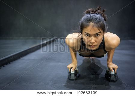 Young Asian athlete woman doing push up with push-up bars on the floor sport and training in fitness gym concepts