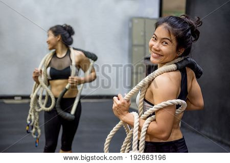 Young Asian gymnast woman smiling while carrying ropes on shoulders for gymnastic exercise in fitness gym