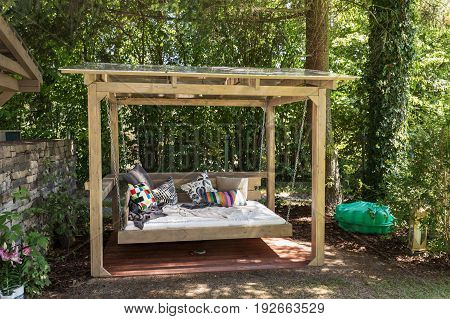 Big swing outdoor bed. Chaise longue in the garden in the pergola. Garden bed with pillows. Big outdoor bed for sunbathing and rest. Four garden bed. Bed in the garden in the pergola.