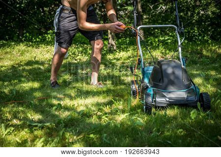 man working with lawn mower on green grass