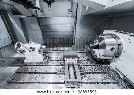 Working area of modern double-spindle CNC metalworking machine. Tinted in cold industrial colors.