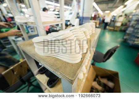 A stack of white shoe soles. Interior of the shoe factory.