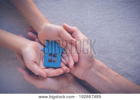 Adult and child hands holding paper house family home homeless shelter and real estate concept