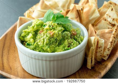Fresh guacamole bowl. Guacamole is a avocado based dip traditionally a mexican (Aztecs) dish. Healthy and easy to make at home with a few simple ingredients. Excellent as party food or at bars..