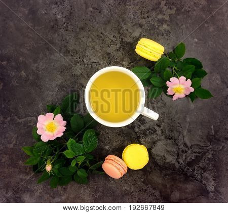 Summer bright composition of cup of herbal tea three macarons dogrose branches and flowers on dark marble table. Flat lay top view