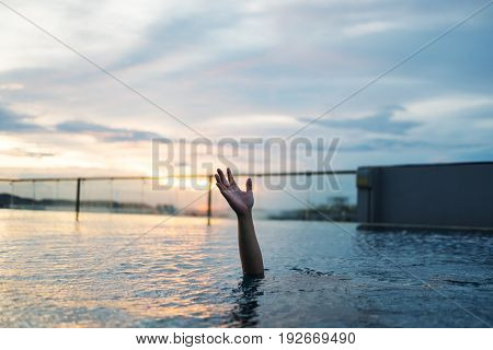 a man drowning in swimming pool at sunset