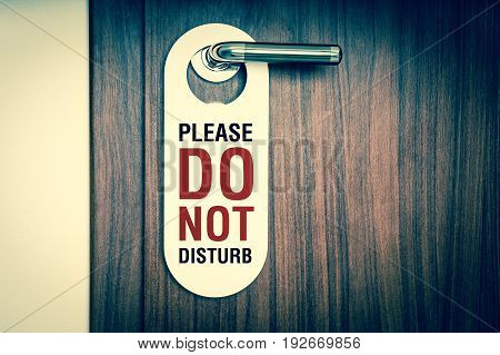 Door of hotel room with sign please do not disturb - retro style