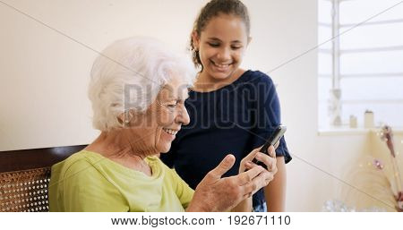 Girl Helps Old Woman Using Mobile Phone And Technology