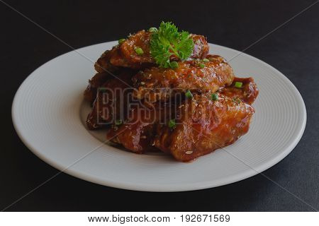 Barbecue chicken wings on white plate served with barbecue dipping sauce. Homemade bbq chicken wing delicious moist and spicy. Barbecue chicken wing isolated background concept. Chicken barbecue on black granite table.