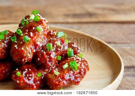 Korean fried chicken wings sprinkled with sesame and spring-onion on wood plate. Homemade Korean barbecue chicken wing delicious moist and spicy. Fried chicken wings in Korean style on wood table. Food background. Chicken wing background.