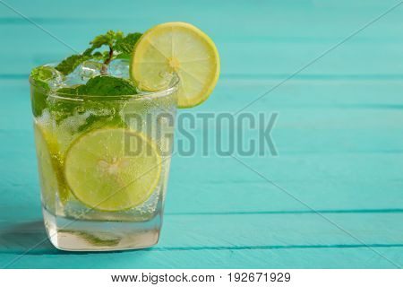 Lemonade in glass on light blue wood table. Lemon or lime and mint leaf in sparkling water or soda. Lemon or lime mojito make fresh and cool for summer. Lemonade or lime juice with copy space. Blue plank background for summer collections.