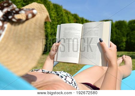Woman lying on lounger in garden and reading a book.