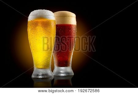 Beer. Cold Craft light and dark Beer in a glass with water drops. Two Craft Beers close up isolated on black background.