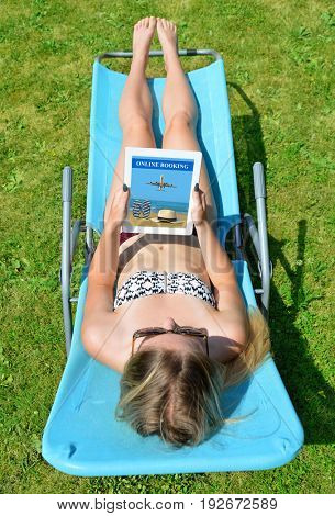 Woman lying on lounger in garden and using digital teblet to book holiday online.