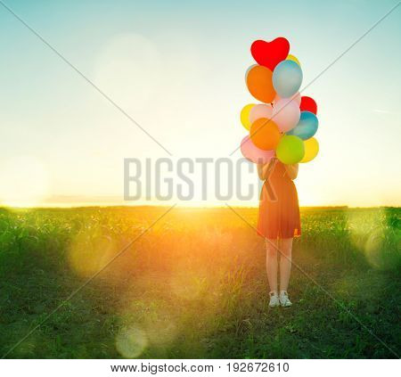 Beauty teenage girl on summer field with colorful balloons over clear sky. Happy young woman enjoying nature outdoors, holding a bunch of colourful air balloons. Sunshine. Sunlight