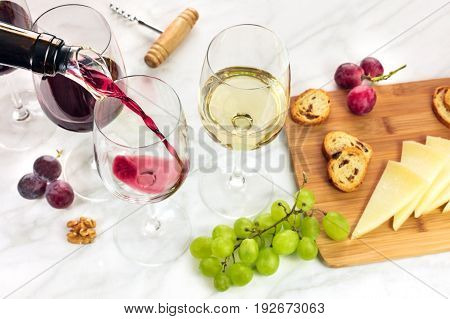 Red wine being poured into a glass with a dispenser at a tasting, with cheese, bread, and grapes. Selective focus